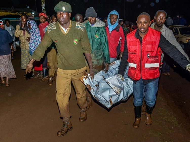 Rescue workers can be seen carrying a victim's body in Solai