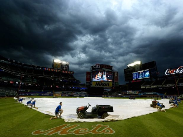 The grounds crew at Citi Field in New York City holds a cover over the baseball field as the storm comes in