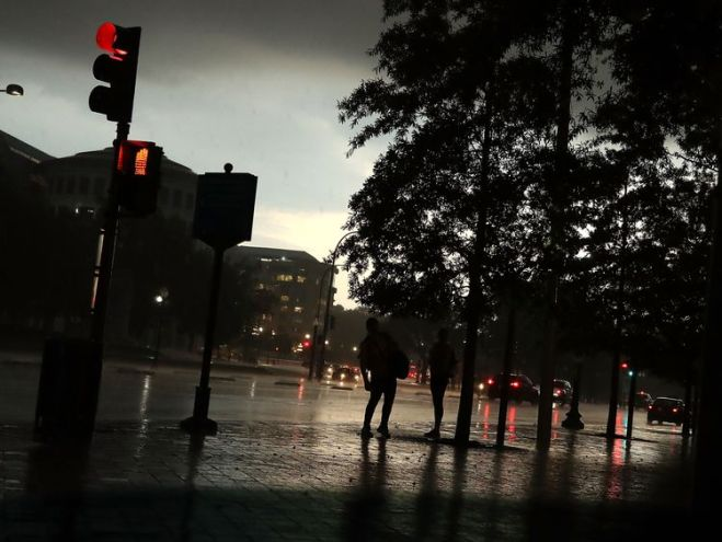 People stand under trees as a severe thunderstorm passes over the US Capitol in Washington DC