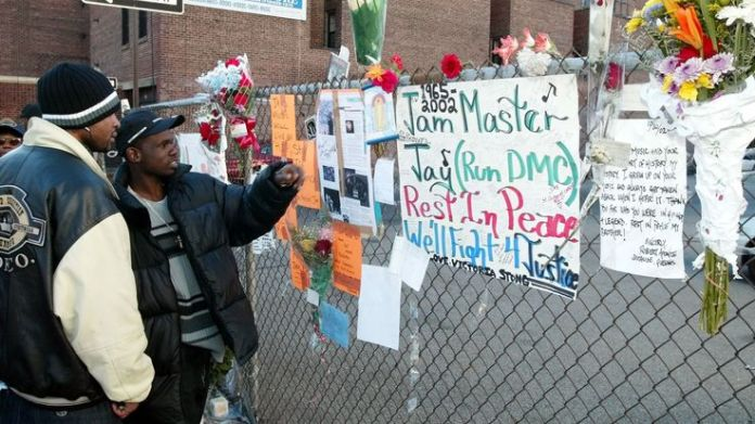 Olel Right (L) and Lionel Frazer (R) look at a wall of flowers and cards outside a music studio in Queens, New York 31 October, 2002 where former Run DMC member Jason Mizell, who was also known as DJ Jam Master Jay, was shot and killed late 30 October. There was no immediate word on the motive for the shooting of Jam Master Jay who was in his studio in New York's Queens neighborhood with another man. The other unidentified man suffers from a wound in the arm. AFP PHOTO/Mat Shootings in the history of rap Shootings in the history of rap skynews jam master jay murders 4340480