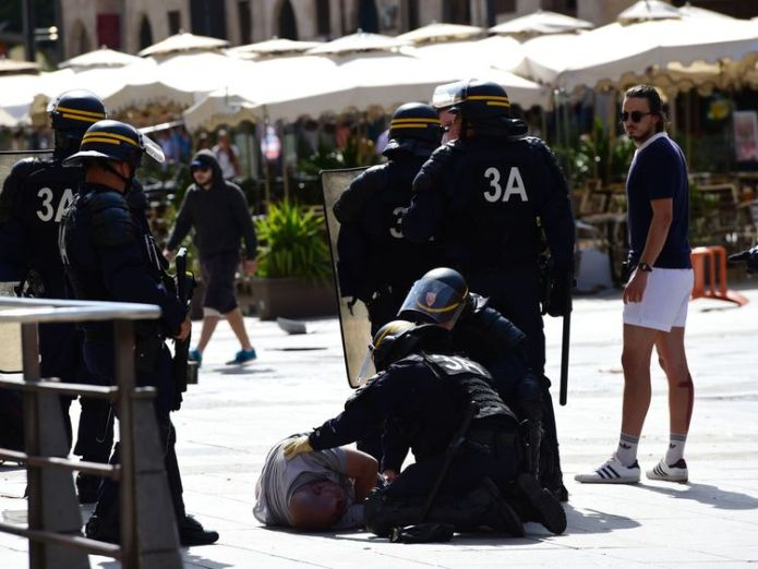 Police personnel attend to injured England fan Andrew Bache following clashes between England fans and police personnel in the city of Marseille, southern France, on June 11, 2016, ahead of the Euro 2016 football match between England and Russia. / AFP / TOBIAS SCHWARZ (Photo credit should read TOBIAS SCHWARZ/AFP/Getty Images) Russia facing battle to keep violent 'ultras' under control Russia facing battle to keep violent 'ultras' under control skynews andrew bache russian ultras 4333521