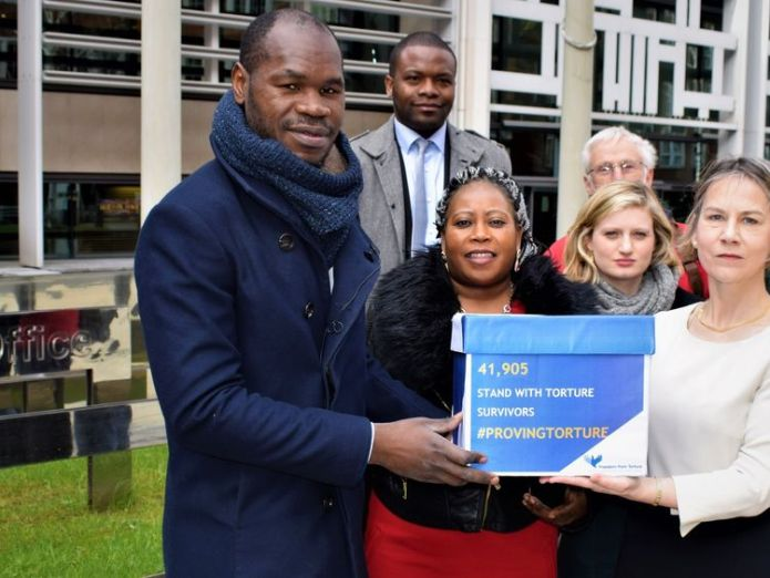 Mr Haoussou hands a petition to former MP Tania Matthias at the home office