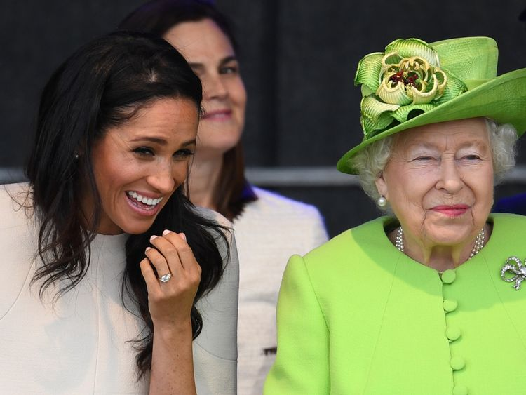 Meghan giggles as she and the Queen sit together