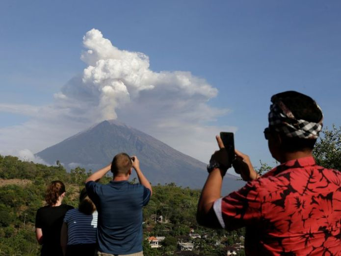 A local guide and foreign tourists take pictures of Mount Agung volcano erupting from Amed, Karangasem Regency in Bali, Indonesia on June 29, 2018. REUTERS/Johannes P. Christo  Volcano eruption leaves thousands stranded in Bali skynews volcano indonesia bali 4348614