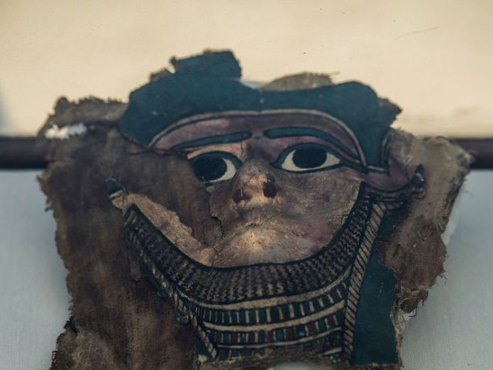 A picture taken on July 14, 2018 shows a broken gilded mummy mask on display in front of the step pyramid of Saqqara, south of the Egyptian capital Cairo. - The Egyptian Minister of Antiquities announced the excavation of a mummification workshop discovered along with a communal burial place, consisting of several burial chambers. The work is being carried out south of the King Unas Pyramid in Saqqara by an Egyptian-German mission. (Photo by Khaled DESOUKI / AFP) (Photo credit should read KHALED  Ancient Egyptian mummification workshop discovered skynews broken mummy mask egypt 4362051