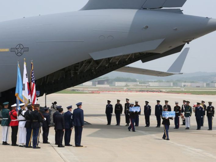 Guards carry boxes containing the remains upon the military plane's return to South Korea