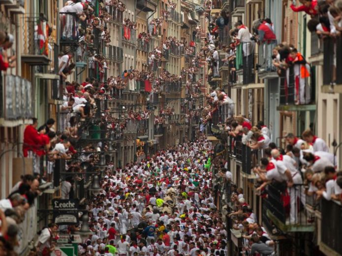 People hang out of their windows to watch the running of the bulls  Man gored and four badly injured on first day of Pamplona bull run skynews pamplona bull run 4356197