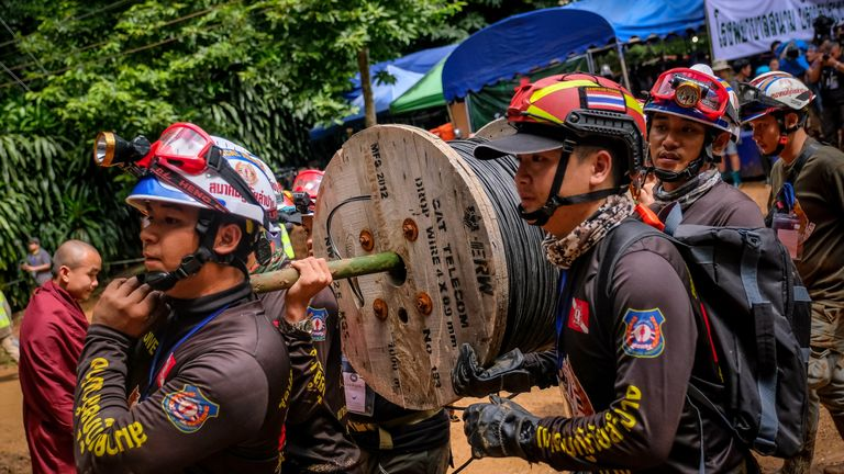 Rescuers carry equipment into the cave complex