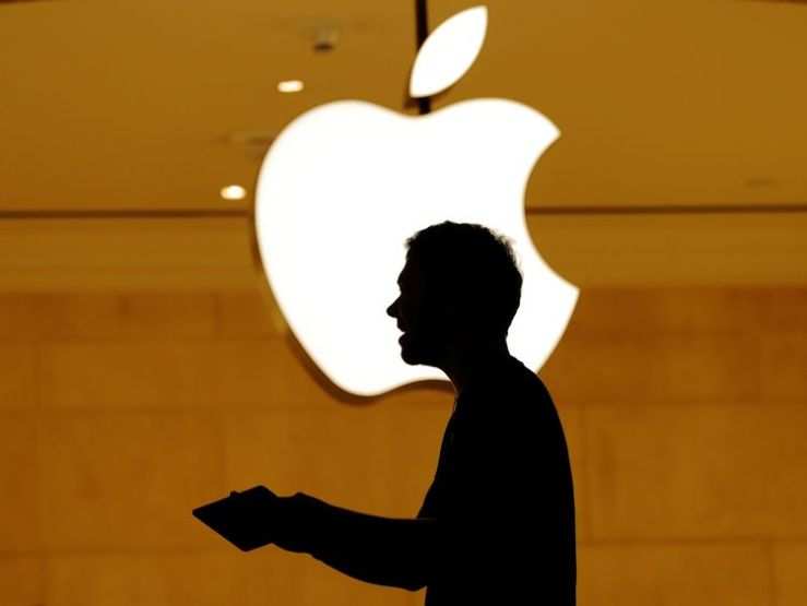 Customers walk past an Apple logo inside of an Apple store at Grand Central Station in New York