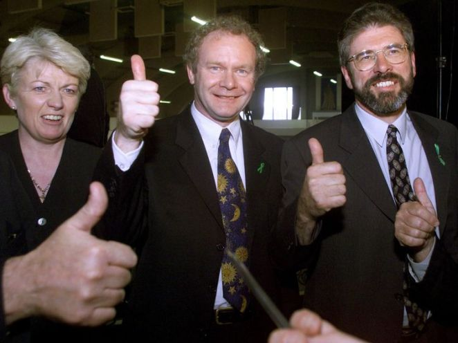 Sinn Fein President Gerry Adams (R) and Martin McGuinness (C) celebrate at Kings Hall in Belfast with a supporter after hearing the result of the Irish referendum in 1998