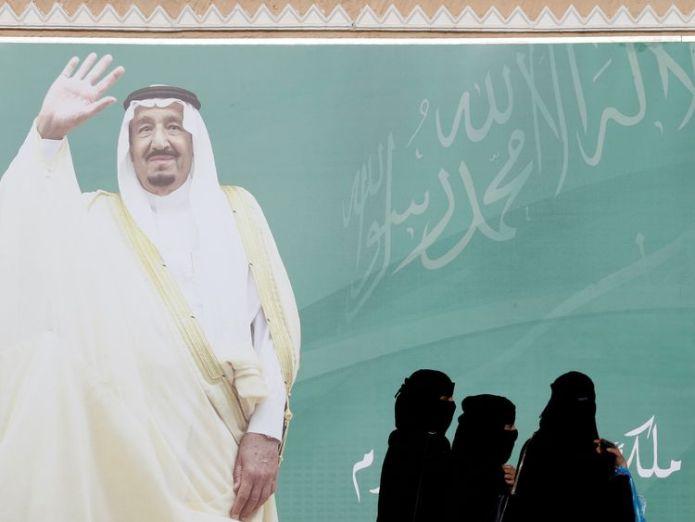 Women walk past a poster of Saudi Arabia's King Salman bin Abdulaziz Al Saud  UK urged to intervene as female Saudi activist becomes 'first to face death penalty' skynews king salman saudi arabia 4397806