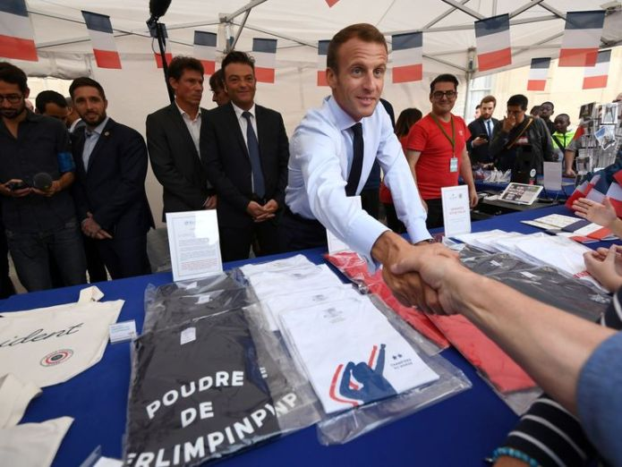 French President Emmanuel Macron shakes hands with visitors next to items for sale at the Elysee Palace   £300k of presidential memorabilia sold in days skynews emmanuel macron elysee palace 4424906