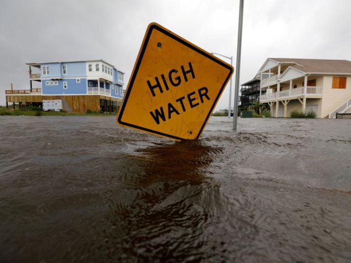 Flood waters lap at a high water warning sign that was partially pushed over by Hurricane Florence on Oak Island, North Carolina  Five arrested for looting as Florence kills 13 in North and South Carolina skynews florence north carolina 4422867