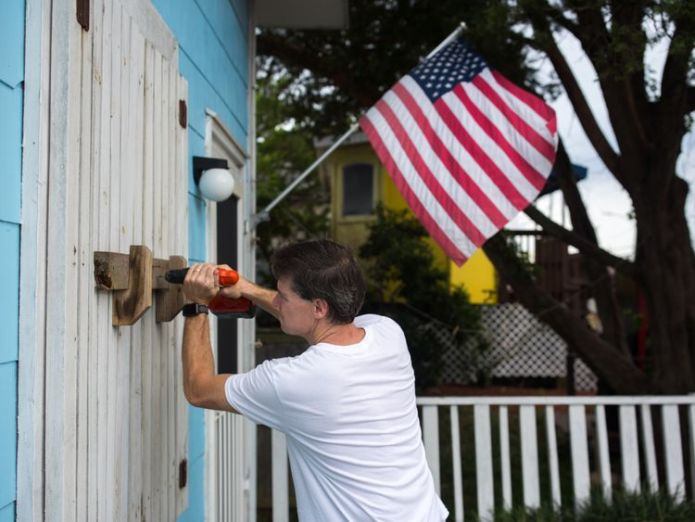 A man helps board up Aussie Island surf shop on September 11, 2018 in Wrightsville, North Carolina in anticipation of Hurricane Florence's high storm surge  Life and death decisions as 'monster' storm looms skynews hurricane florence 4418091