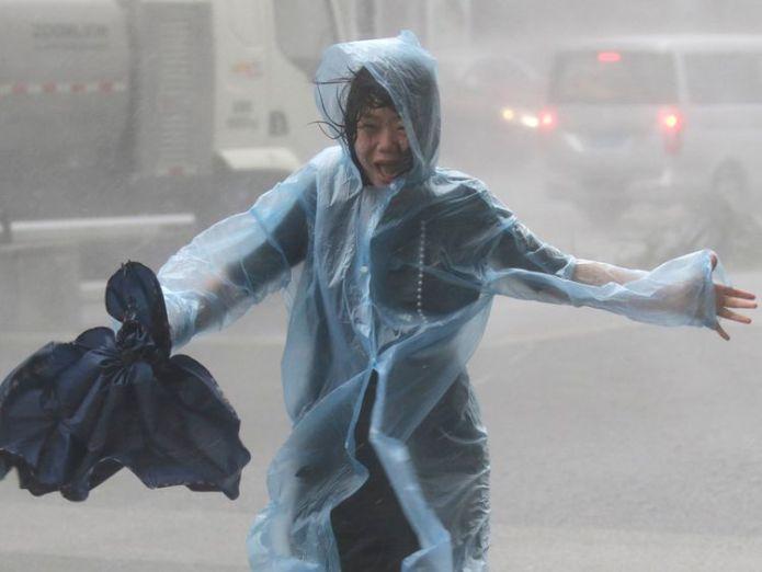 A woman runs in Shenzen as Typhoon Mangkhut arrives in China  Typhoon Mangkhut leaves 28 dead in trail of destruction across Philippines skynews typhoon mangkhut shenzen 4422654