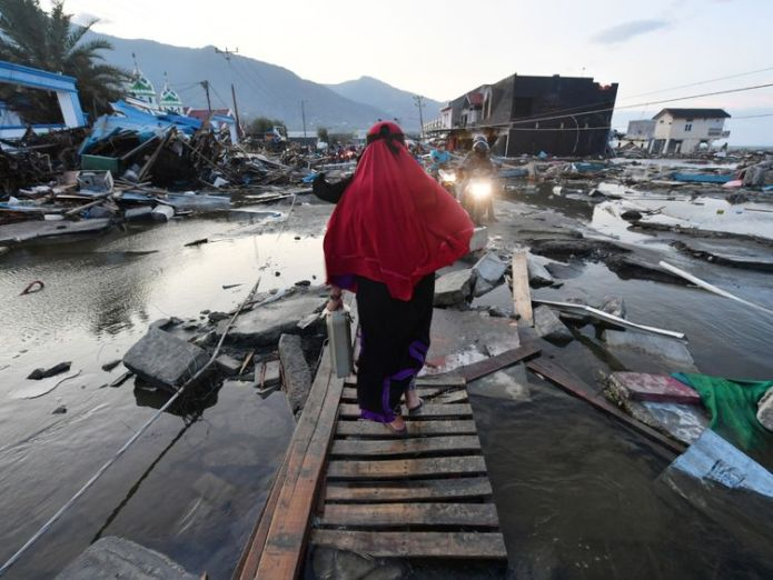 A woman walks through a devastated area in Palu, in Indonesia's Central Sulawesi   Volcano erupts on quake-hit Indonesia island skynews indonesia sulawesi 4441393