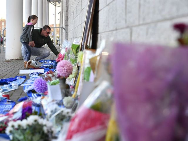 A man and a girl add to flowers and Leicester City scarfs left as tributes