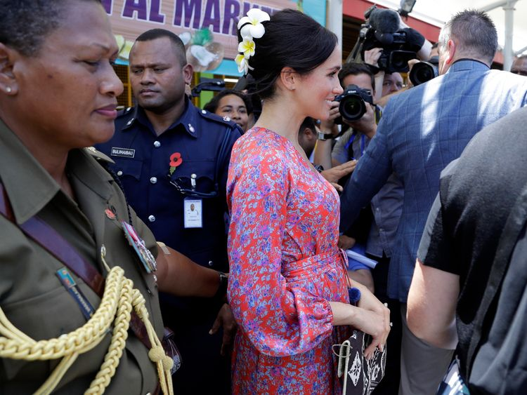 Meghan smiled defiantly throughout while visiting the crowded market