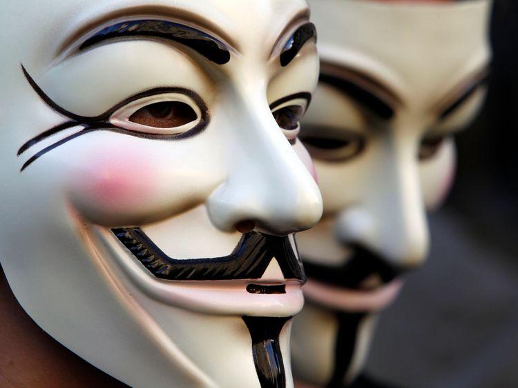 Demonstrators wearing anonymous masks