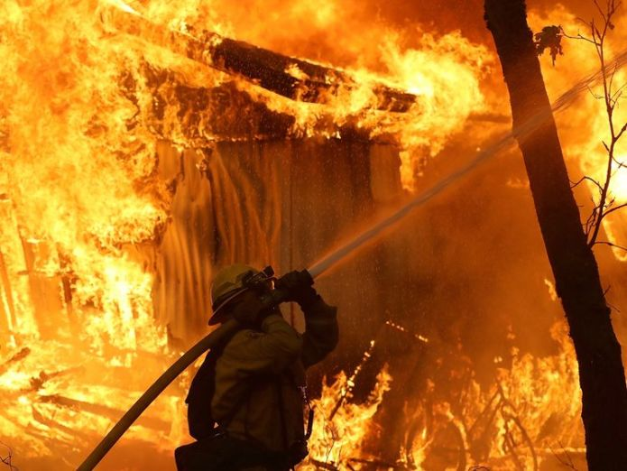 A firefighter battles a wild fire blaze in Magalia, California  At least five people killed in their cars as California wildfires spread and Malibu is evacuated skynews california wildfires 4482175