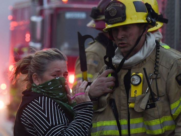 A local resident speaks with firefighters stationed along Pacific Coast Highway (Highway 1) to battle the Woolsey Fire on November 9, 2018 in Malibu, California
