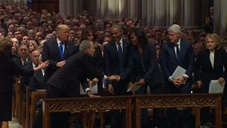 George W Bush slips Michelle Obama a piece of candy as a kind gesture at the state funeral for his father, George HW Bush.