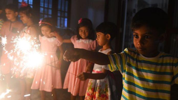 A child holds a sparkler during New Year's celebrations in Colombo, Sri Lanka, on January 1, 2019. (Photo by ISHARA S. KODIKARA / AFP) (Photo credit should read ISHARA S. KODIKARA/AFP/Getty Images)