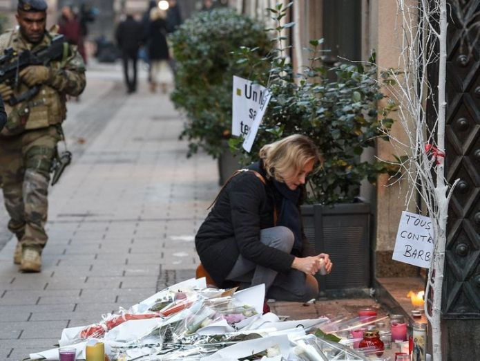 A French soldier walks past a woman lighting a candle in the street