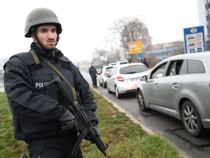 Members of the German police search all the vehicles driving towards the border between France and Germany