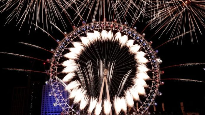 Fireworks explode over The London Eye and Elizabeth Tower near Parliament as thousands of revelers gather along the banks of the River Thames to ring in the New Year on January 1, 2019 in London, England