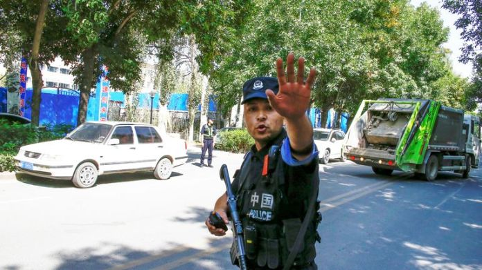 A Chinese police officer at a roadblock near what is officially called a vocational education centre in Xinjiang