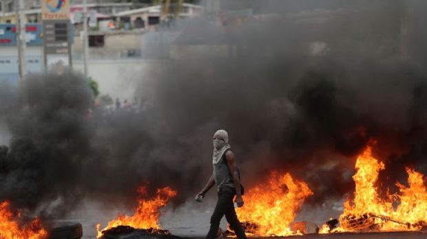 A demonstrator walks past a burning barricade during protests on 15 February