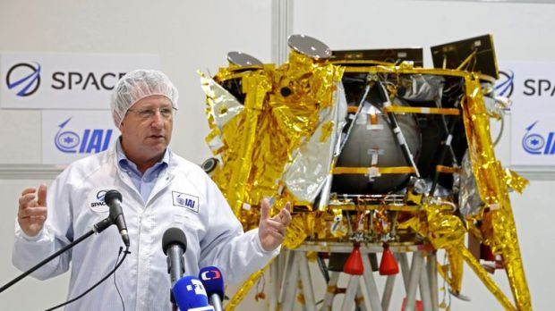 Israeli Aerospace Industries director of Space division Opher Doron speaks in front a a spacecraft weighing some 585 kilogrammes (1,300 pounds) during a presentation by Israeli nonprofit SpaceIL and Israeli state-owned Aerospace Industries, on December 17, 2018 in Yehud, east of Tel Aviv. - Israeli scientists making final preparations to launch the country's first spacecraft to the moon added a special passenger that will accompany the journey. A time capsule of three digital discs containing th