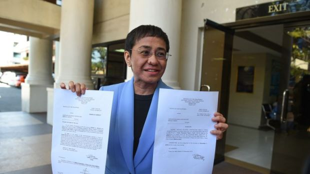 Maria Ressa in 2018 with her arrest warrant for a tax fraud charge