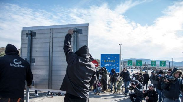 Workers erect a new sign on North Macedonia's border with Greece