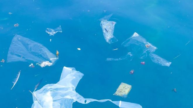 Plastic bags and debris floating in the sea - Stock image
