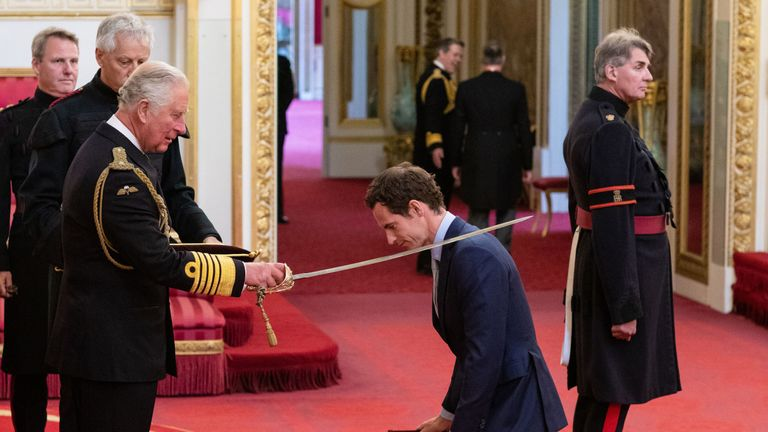 Andy MNurray kneels as he receives his knighthood from Prince Charles