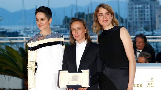 """CANNES, FRANCE - MAY 25: Celine Sciamma (C), winner of the Best Screenplay award for her film """"Portrait de la Jeune Fille en Feu"""", poses with Noemie Merlant (L) and Adele Haenel (R) at thewinner photocall during the 72nd annual Cannes Film Festival on May 25, 2019 in Cannes, France. (Photo by John Phillips/Getty Images)"""