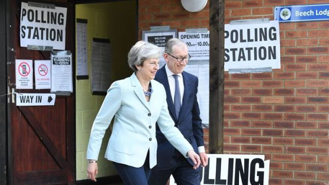 Theresa May and her husband Philip leave her local constituency polling station in Sonning, Berkshire