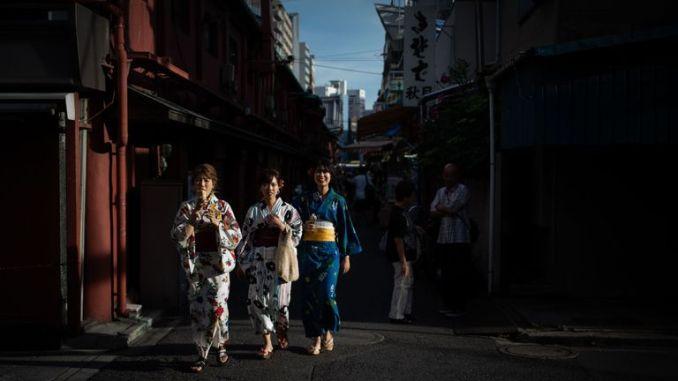 Women wearing kimonos walk along a street in Tokyo's Asakusa district