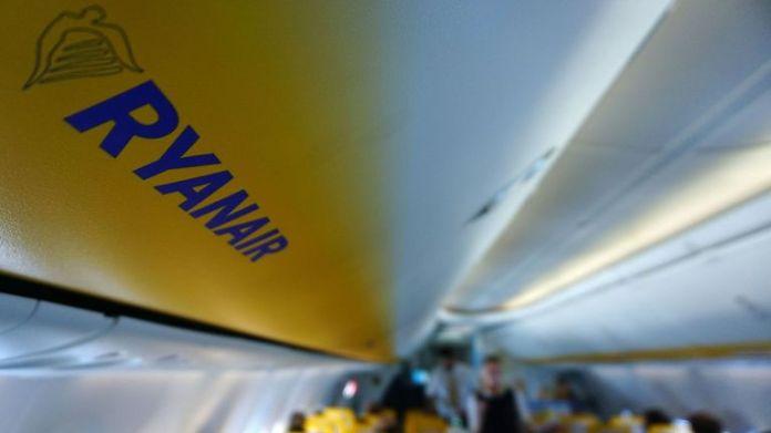 Una imagen muestra el logotipo de Ryanair como un tablero de pasajeros dentro de un avión de Ryanair