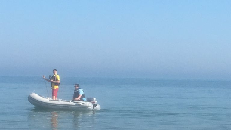 A couple of officials in a dinghy warn people to get out of the water at the sea in Frinton, Essex, as emergency services received several reports of people coughing and struggling to breathe
