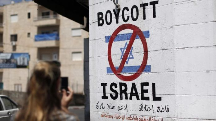 A tourist photographed a panel painted on a wall in the West Bank city of Bethlehem on June 5, 2015, calling for boycotting Israeli products from Jewish settlements. The international BDS campaign (boycott, divestment and sanctions), which campaigns for a ban on Israeli goods, aims to exert political and economic pressure on Israel's occupation of the Palestinian territories in order to reiterate the success of the campaign ended to apartheid in South Africa.
