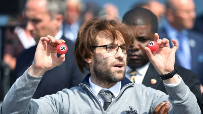 Comedian Lee Nelson/ Simon Brodkin is taken away by security while holding golf balls stamped with swastika as he protests against Donald Trump at his Trump Turnberry Resort in June 2016 in Ayr, Scotland