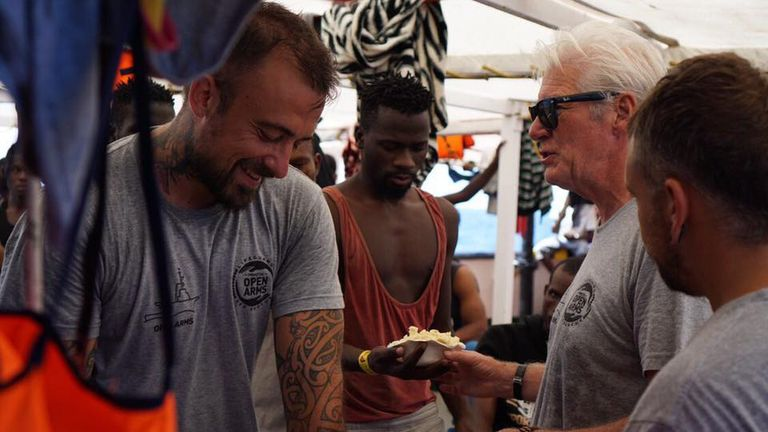 American actor Richard Gere sharing a meal with migrants aboard a ship that has rescued 121 people from the sea