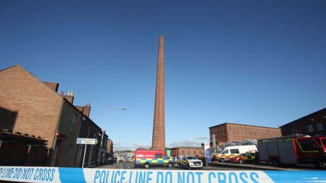 Emergency vehicles block the road near to Dixon's Chimney in Carlisle, Cumbria, where a man, whose condition is currently unknown, continues to hang upside down from the top of the chimney 270ft up.