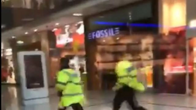 Police running through the Arndale Centre in Manchester. Pic: @GrizzleMarine /PA Wire