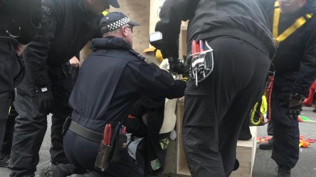 Specialist police officers free a protester who chained himself to a wooden structure