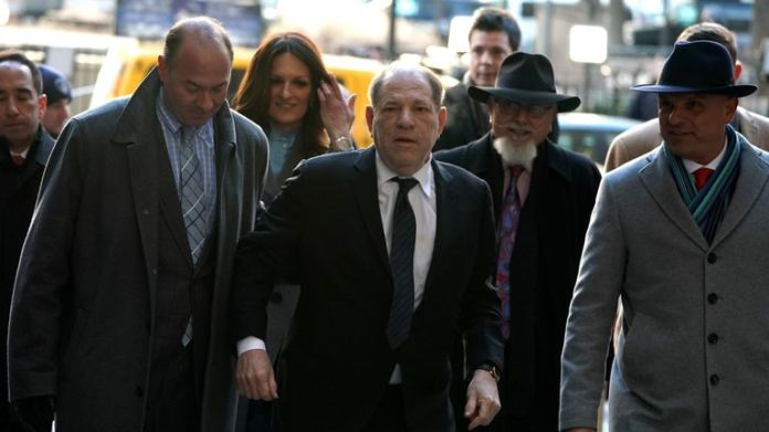 """Harvey Weinstein(C) arrives at the Manhattan Criminal Court, on January 22, 2020 for opening arguments in his rape and sexual assault trial in New York City. - Opening arguments in Harvey Weinstein's rape and sexual assault trial are due Wednesday, with the defense expected to detail """"loving"""" emails between the once-mighty movie producer and his accusers. Weinstein, 67, faces life in prison if convicted of predatory sexual assault charges related to two women in the high-profile New York proceedings seen as key to the #MeToo movement. (Photo by TIMOTHY A. CLARY / AFP) (Photo by TIMOTHY A. CLARY/AFP via Getty Images)"""