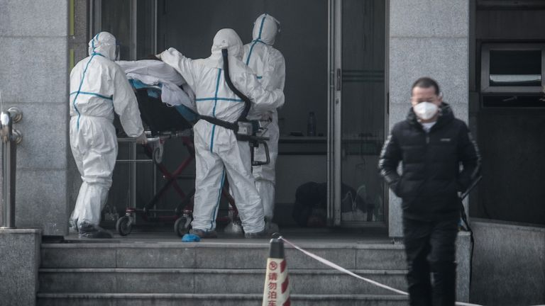 Medical staff carry a patient with the new coronavirus into Wuhan's Jinyintan hospital